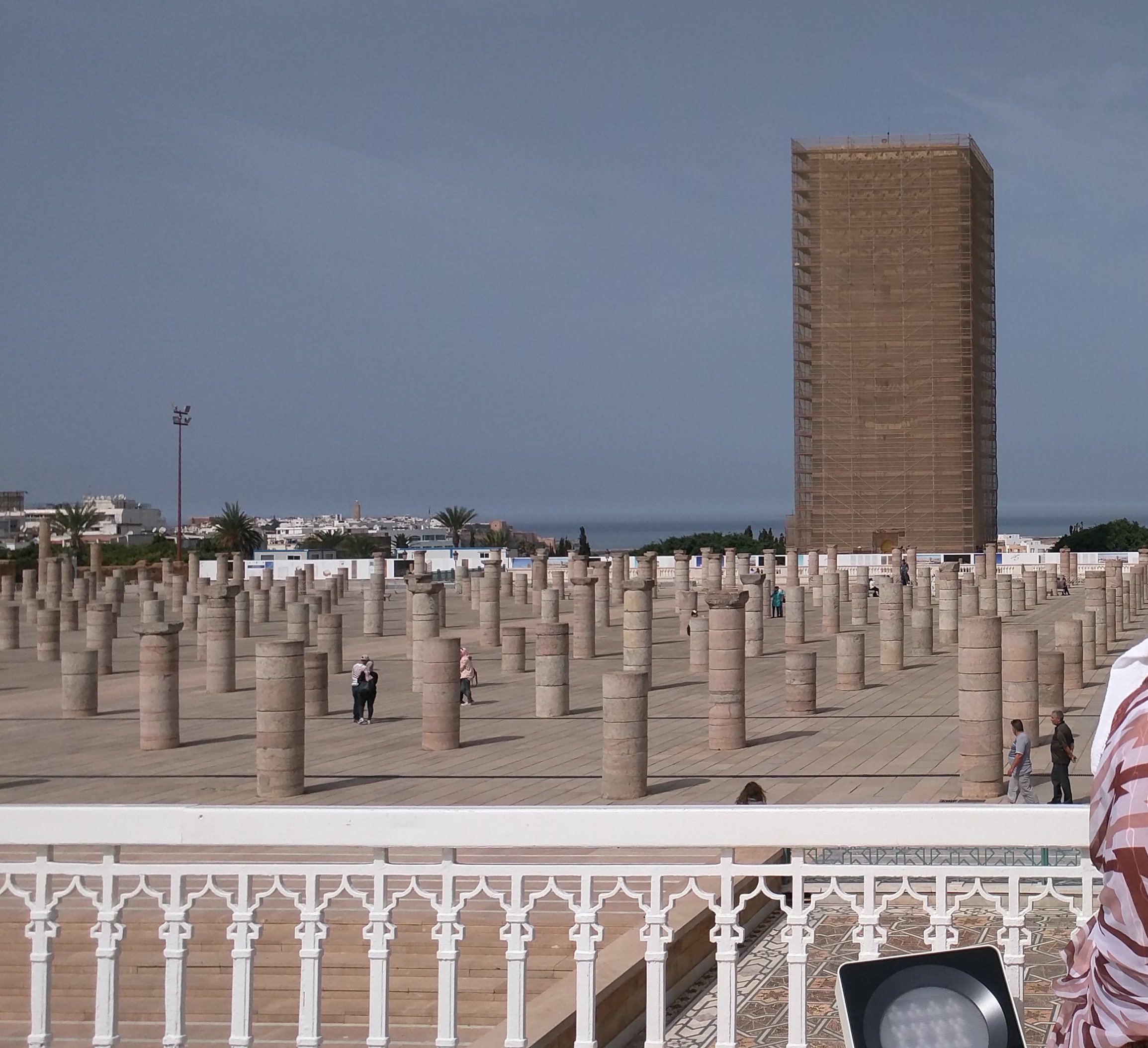 Outside Mausoleum of Mohammed V.  Hassan Tower in the background. Currently under renovation, so covered in scaffolding.